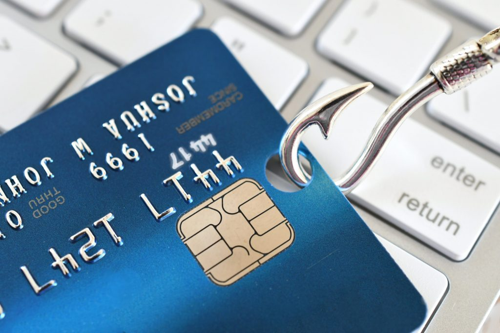Phishing scam fraud identity theft concept - credit card on fishing hook on white computer keyboard